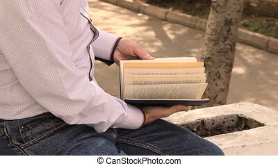Man leafing through pages of a book,  outdoors