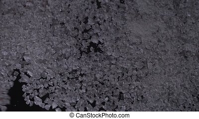 Man hand removing coarse salt pile, black background clip
