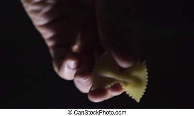 Man hand putting down a piece of farfalle pasta and rotating...