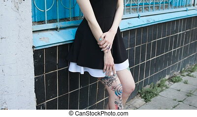 Portrait of a punk girl with tattooed feet on the street. A...