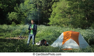 Man talking on the phone near campfire and tents in the...