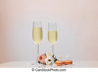 Two glasses with champagne, boutonniere with roses and...