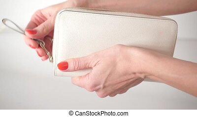 Girl with red nail polish closing her empty white purse clip