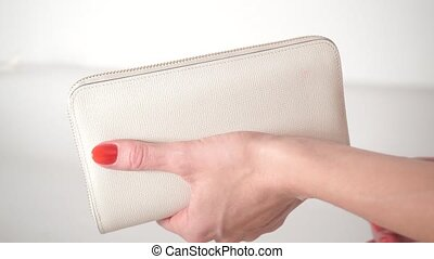 Girl with red nail polish opening her empty white purse
