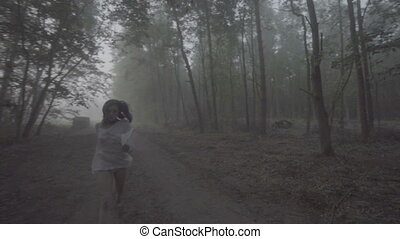 Woman running in forest, front view - Front view of...