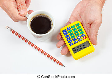 Hands holding a digital calculator and cup of coffee on...