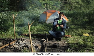 A man playing on a tablet in the game near the campfire and tents. In the forest morning