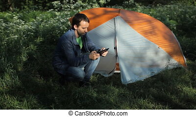 Man photographs on a the tablet next to a tent in the forest