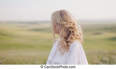 Girl in a field turn round and looking at the camera