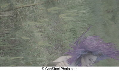 Woman falling down on the grass - Beautiful woman in purple...