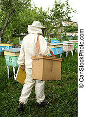 beekeeper in protective suit works on an apiary