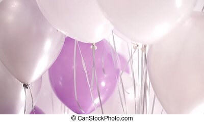 Many white, pink and silver helium balloons floating in the...