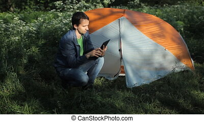 A man sits near the tent and making a video call on the tablet. Morning in the forest