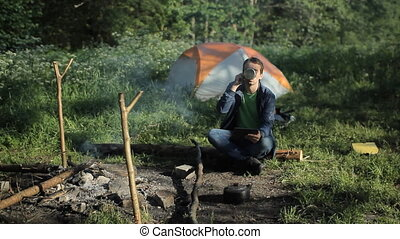 A man makes a video call on the tablet. Near the fire is burning and is tent in the forest