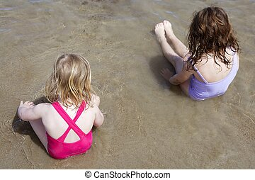 two sisters sit on beach bathing suit swimsuit back view...