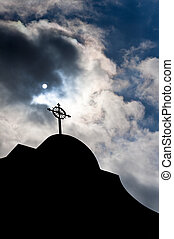Religious Turmoil - The cross on a church against turbulent...