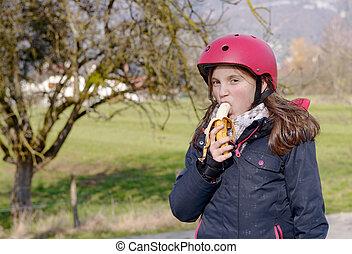 preteen with roller skate helmet, eat banana