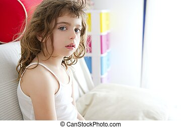 little burnette girl sits on sofa in window light
