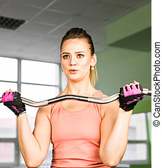fitness, sport, training and lifestyle concept - happy woman with barbell flexing muscles in gym