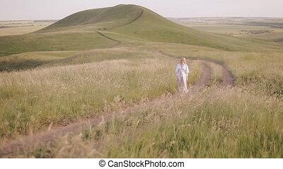 woman in white dress walking in the field