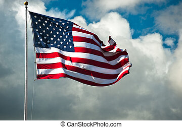 Windblown Flag - American flag against a cloudy sky on a...