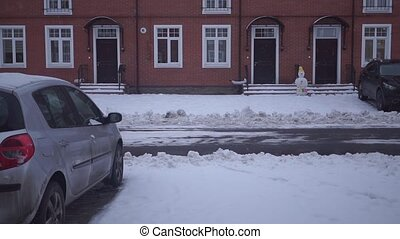 Snowing in front of red brick townhouses clip