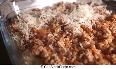 Making homemade lasagna. Pouring grated cheese. Part of a...