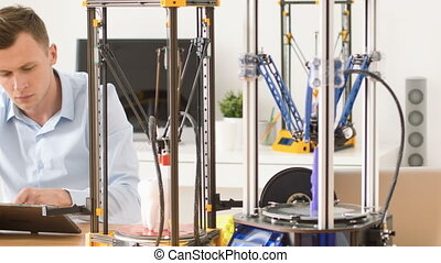 Serious man working with 3d printer - Professional worker...