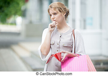 Pensive young woman out of cash after shopping - Portrait of...