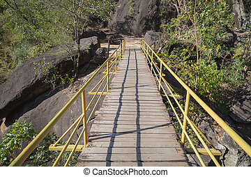 Bridge cross mountains - Wooden bridge with yellow iron...