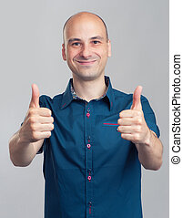 successful man gesturing his thumbs up