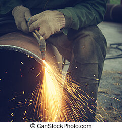 Metal cutting with acetylene torchStaraya rusty pipe