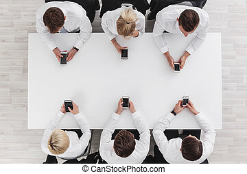Business people with cell phones - Business people sitting...