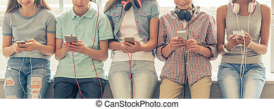 Teenagers with gadgets - Cropped image of group of teenage...
