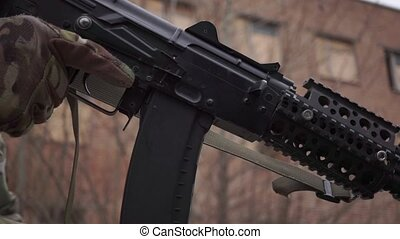 Changing a magazine of Kalashnikov assault rifle. Close up...