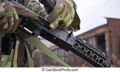 Attaching a magazine to assault rifle. Close up shot of...