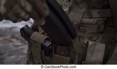 Soldier puts assault rifle ammo into pockets of his ammo...