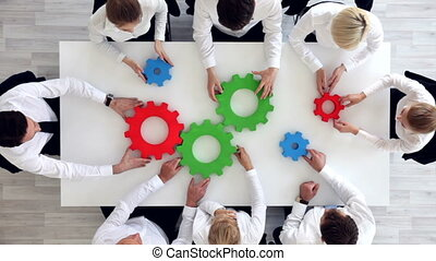 Business team with cogs - Business team sitting around the...