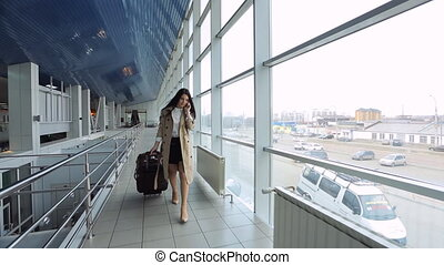 Woman in beige coat talks on phone and goes through airport....