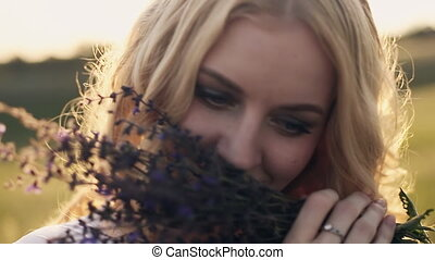 blonde girl with blue eyes smelling a herbs bouquet - blonde...