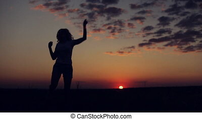 silhouette of girl dances and shake on sunset background