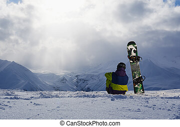 Snowboarder sitting on the snow and admiring the winter...