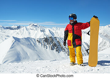 snowboarder standing with board high in the mountains i -...