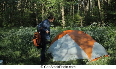 The man removes a backpack near the tent. Trying to find something. Early morning in the forest
