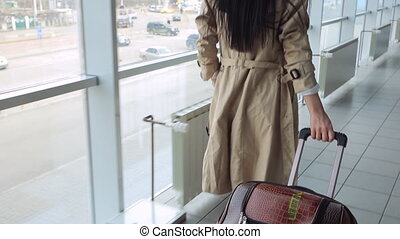 Lady in beige coat with black hair carries suitcase