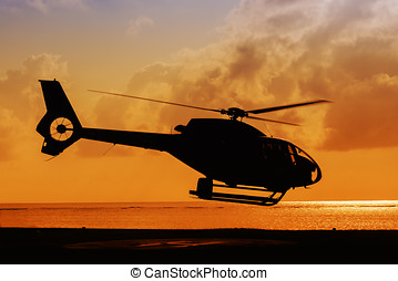 helicopter taking off at sunset - silhouette of helicopter...