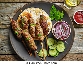 grilled minced meat skewers kebabs on wooden table, top view