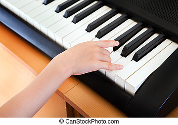 Hand on the Keyboard - Hand of the Kid on the Piano Keyboard