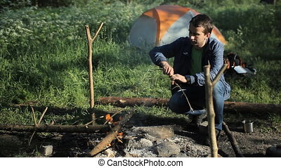 Man throws wood on the fire in the camping. Early morning in...