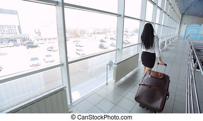 Pretty young woman walks through airport with luggage